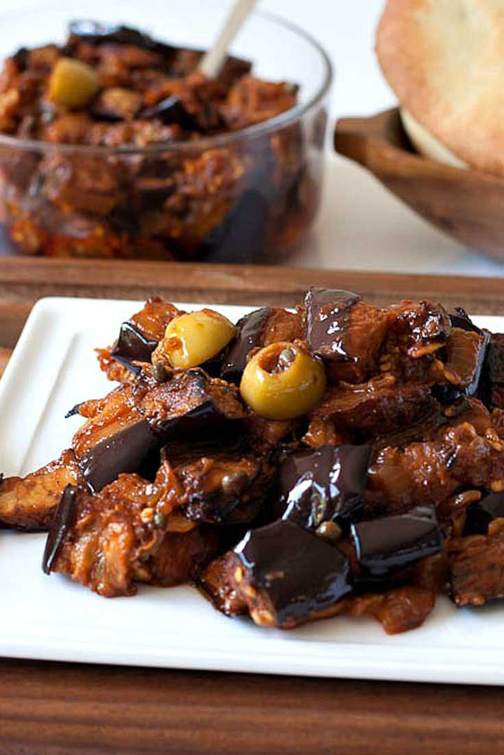 Caponata is a Sicilian eggplant dish consisting of a cooked vegetable salad made from chopped fried eggplant and celery seasoned with sweetened vinegar, with capers in a sweet and sour sauce. #italian #eggplant