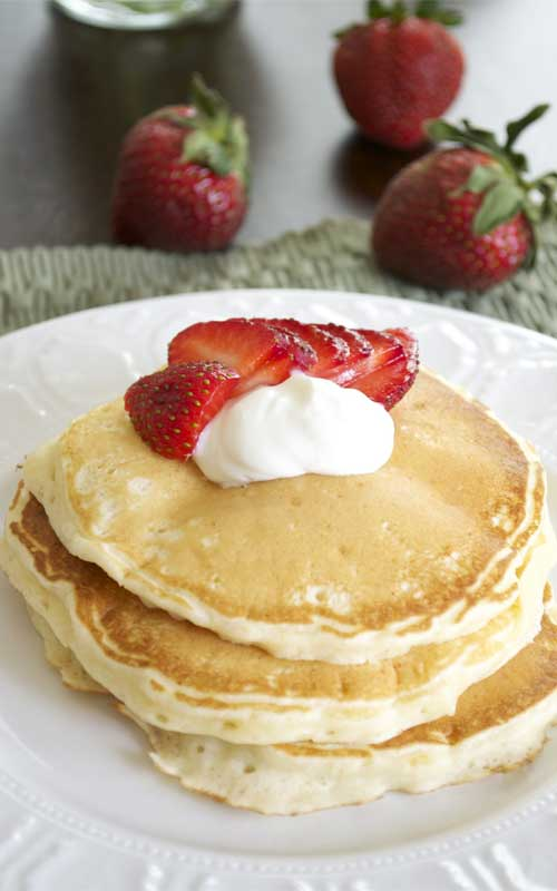 Strawberries and Cream Cheesecake Pancakes Recipe - You will love these pancakes because the are light, fluffy and you don't need any syrup. The yogurt cream and fresh strawberries provide a nice balance of flavors and freshness.