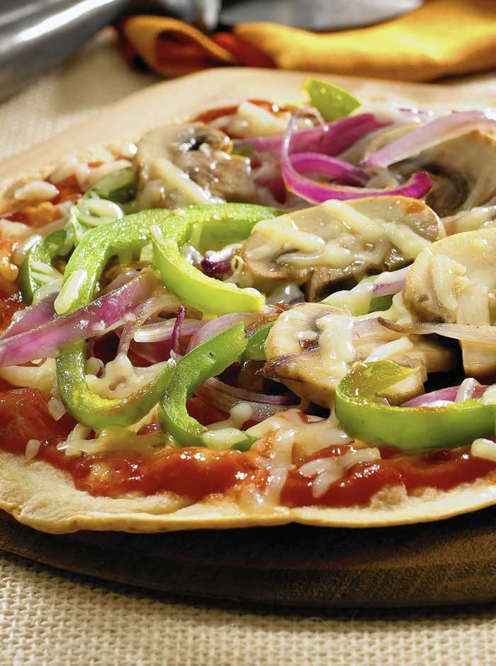 "Next time they ask for pizza, you can feel good about saying ""yes!"", with this Skinny Pizza recipe. Flour tortillas make for a crispy crust, perfect for loading with tomato sauce, cheese, and lots of fresh veggies."